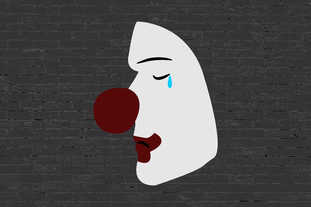 Bob Burnham als trauriger Clown vor einer grauen Mauer